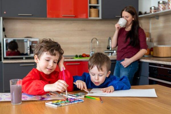 skupione dzieci malują, mama pije kawę